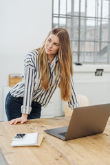 Young woman leaning against desk with laptop