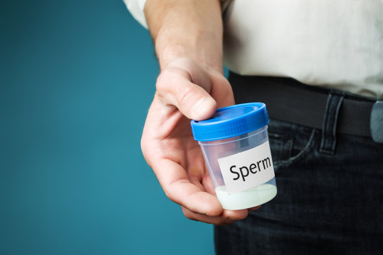 Container with sperm in a man's hand. Concept of donating sperm and testing fertility