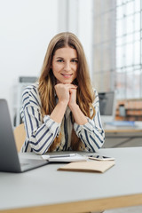 Young smiling woman sitting at desk in office