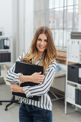 Attractive businesswoman clasping a large binder