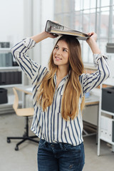Young cheerful girl with file binder on her head