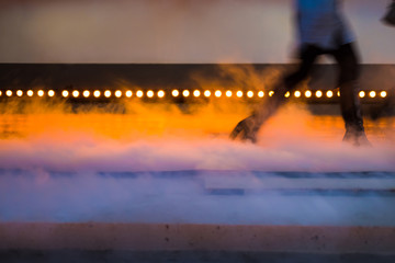 Fashion show, catwalk runway show event - upper half of a model passing lights with smoke in the foreground