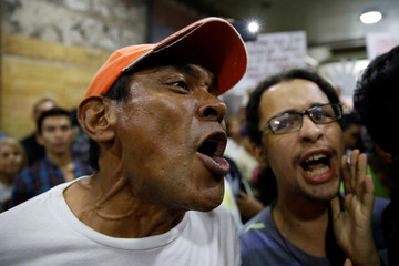 People shout slogans during a protest due to the shortage of medicine, outside the Health Ministry in Caracas