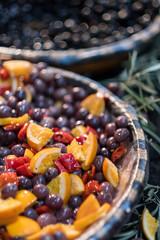 red kalamata olives marinated in oil decorated with oranges and peppers on display at market