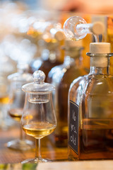 """Whiskey or whisky tasting: Bottles with glasses - the jars are still covered in order to preserve the aroma - are waiting for connoisseurs to taste them. The foremost bottle is labelled """"16 yrs. old"""""""