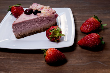 Strawberry cheesecake on black plate over rustic wooden background. Top view