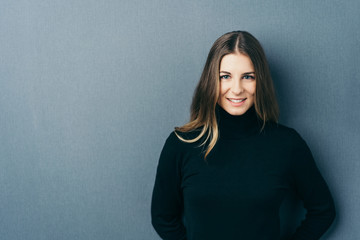 Young smiling woman wearing black roll neck jumper