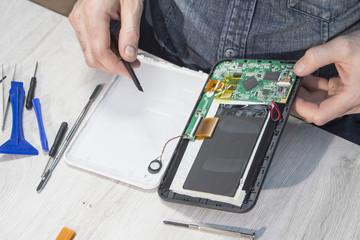 Fototapeta Naprawa tabletu w serwisie. Rozkręcanie tabletu przez pracownika. obraz