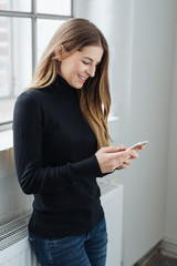 Trendy slender young woman texting a message
