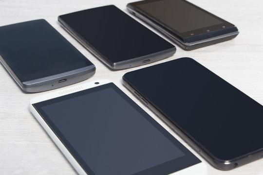 Smartfony ułożone na blacie jeden obok drugiego.