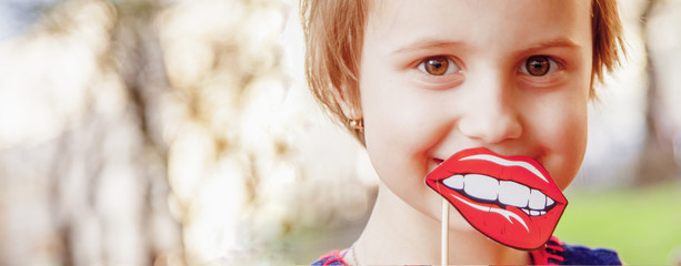Funny beautiful little child girl playing with fake lips outdoors