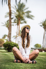 Portrait of cheerful young woman in summer hat and sunglasses under palm tree on green grass. Summer vacation
