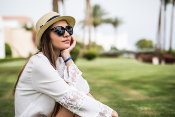 Cheerful young woman in hat and sunglasses sitting on grass on summer resort palms background. Summer vocation