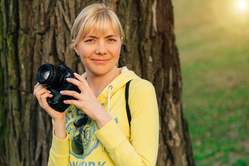 Girl with professional camera in hands. Close up of female photographer in park.