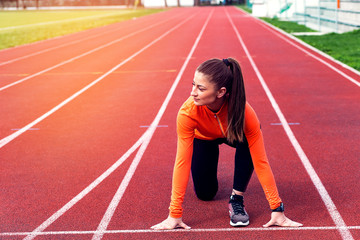 Focused sports women in running start position on racetrack