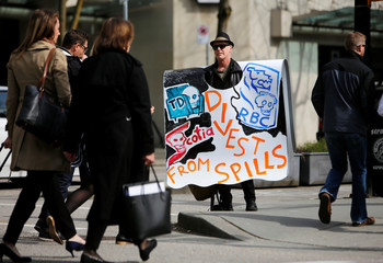 A man wears a sign protesting Kinder Morgan's Trans Mountain pipeline outside the British Columbia Supreme Court, in Vancouver