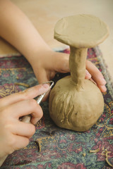 Child sculpts the product from raw clay