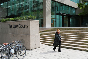 Guul Kiit Jaad of the Haida First Nation walks out of the British Columbia Supreme Court after her first court appearance for protesting Kinder Morgan's Trans Mountain pipeline in Vancouver