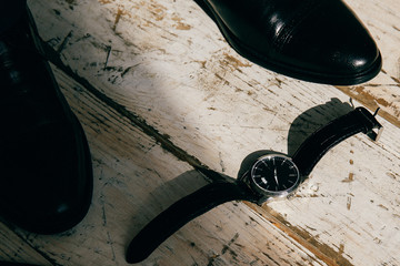 Watches, men's shoes on wooden background
