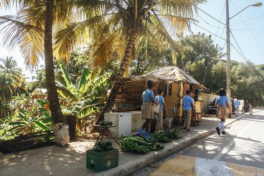 Children in school uniforms go home. Dominicana