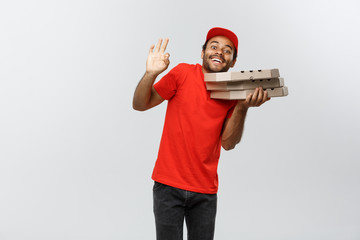 Delivery Concept - Portrait of Handsome African American Pizza delivery man. Isolated on Grey studio Background. Copy Space.