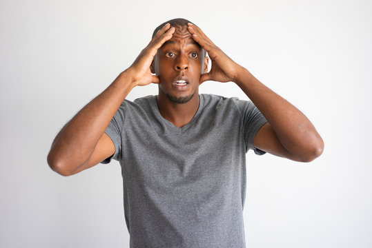 Portrait of stressed and desperate African American. Frightened black man in grey tshirt upset with unexpected problems and touching head. Shock and bad news concept