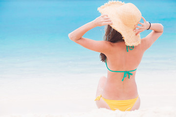 portrait of young woman l in bikiniand straw hat on tropical Maldives beach
