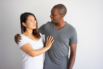 Romantic portrait of interracial couple smiling to each other. Young African man hugging his Asian girlfriend, they discussing something. Love and international family concept