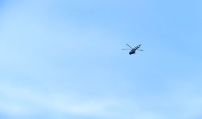 the military helicopter in the blue sky above me high, high in the sky aviation