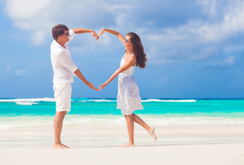 young happy couple in white making heart shape on tropical beach. honeymoon