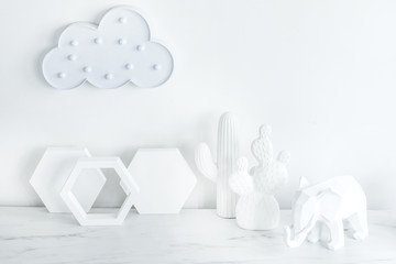 Creative desk with copy space , cacti, elephant figure. White concept of wall with hexagone shapes and cloud.