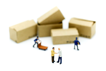 Miniature people : businessmen hand checking, standing in front of  Worker and box using as background shipping, rent container, business concept.