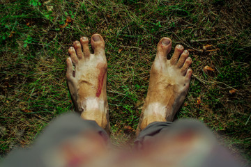 point of view of a man standing barefoot on a ground with green grass and moss