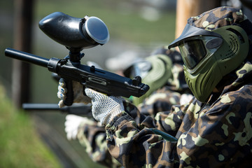 Boy in camouflage suit stands against the paintball area with his paintball gun up and looks straight ahead