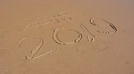 Happy New Year 2019 replace 2018, lettering on the beach. New Year 2019 is coming concept.