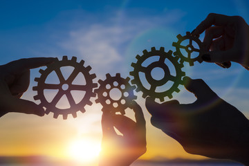 gears in hands on sunset background. teamwork.business partnership.