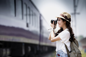 Young beautiful woman traveler with backpack holding vitage camera and taking photos a train