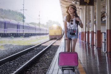 Young beautiful woman with pink luggage walking on platform of railway station