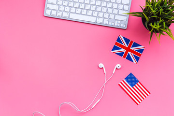 Learn english online. Computer keyboard, headphones, british and american flags on pink background top view copy space