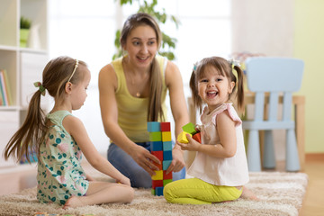 Happy family playing with cubes on the floor. Mother and children daughters spend fun time together.