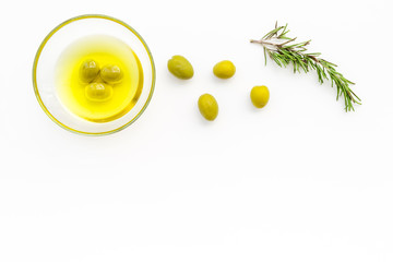 Make olive oil concept. Green olives in bowl with olive oil on white background top view copy space