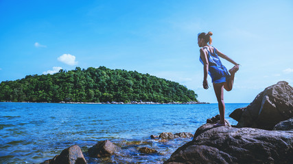Asian women relax in the holiday. Travel relax.  Play if yoga. On the rocks by the sea. In the summer. Thailand