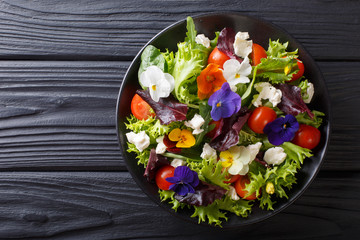 Fresh organic salad from edible flowers with lettuce, tomatoes and cream cheese close-up. Horizontal top view