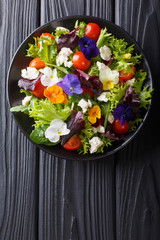 Fresh organic salad from edible flowers with lettuce, tomatoes and cream cheese close-up. Vertical top view