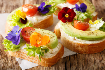 Beautiful sandwiches with avocado, tomatoes, edible flowers of viola and cream cheese close-up on the table. horizontal