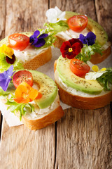 Vegetarian open sandwiches with avocado, tomatoes, edible flowers and cream cheese close-up. vertical