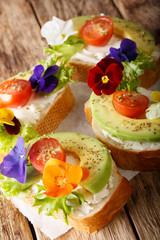 Healthy food: toasts with avocado, tomatoes, edible flowers and cream cheese close-up. vertical