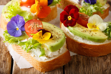 Festive toasts with avocado, tomatoes, edible flowers and cream cheese close-up. horizontal