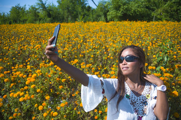 happy and beautiful young Asian tourist woman taking selfie pic in gorgeous orange marigold flowers field natural landscape in travel excursion