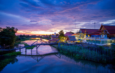 Wall Mural - The view of countryside among natural small creek with old temple, old wooden bridge and beautiful sky during sunset in Suphanburi, Thailand.